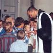 Schuleingang 2003 - Pfarrer Führer zeigt den Kindern etwas spannendes!